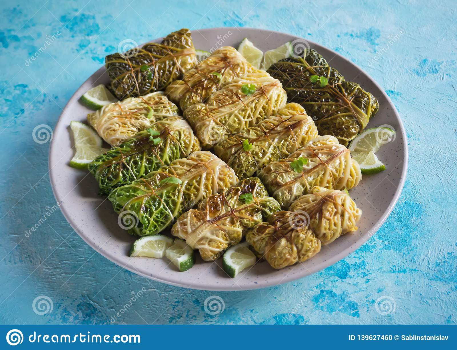 Juicy stuffed cabbage in a plate on a blue table.