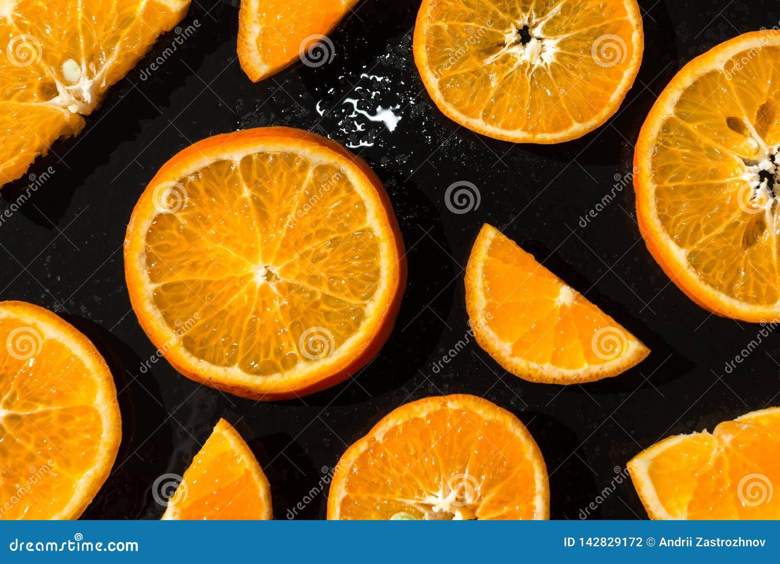 Juicy tangerines, sliced on a black background