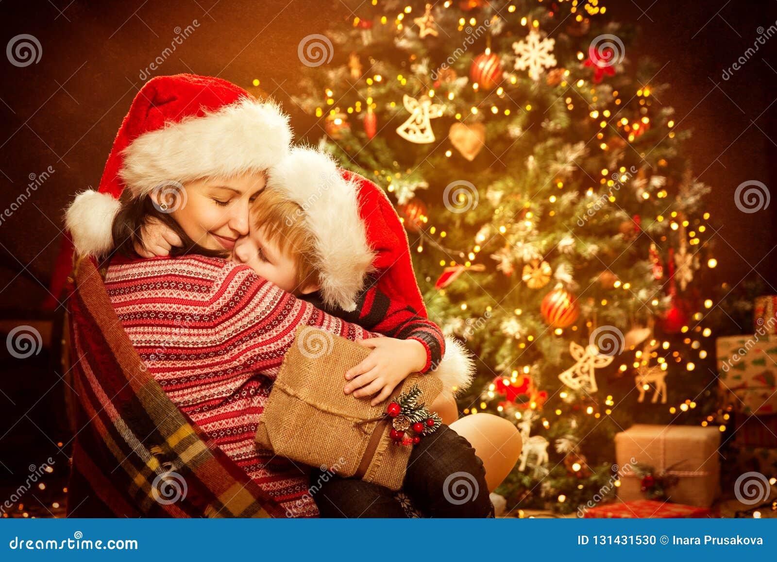 Jul familj och Xmas-trädet, den lyckliga modern att ge sig behandla som ett barn barnet gåvagåvan för det nya året