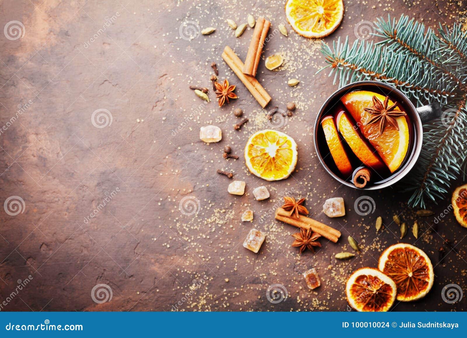 Jul funderade vin eller gluhwein med kryddor och apelsinskivor på lantlig bästa sikt för tabell Traditionell drink på vinterferie