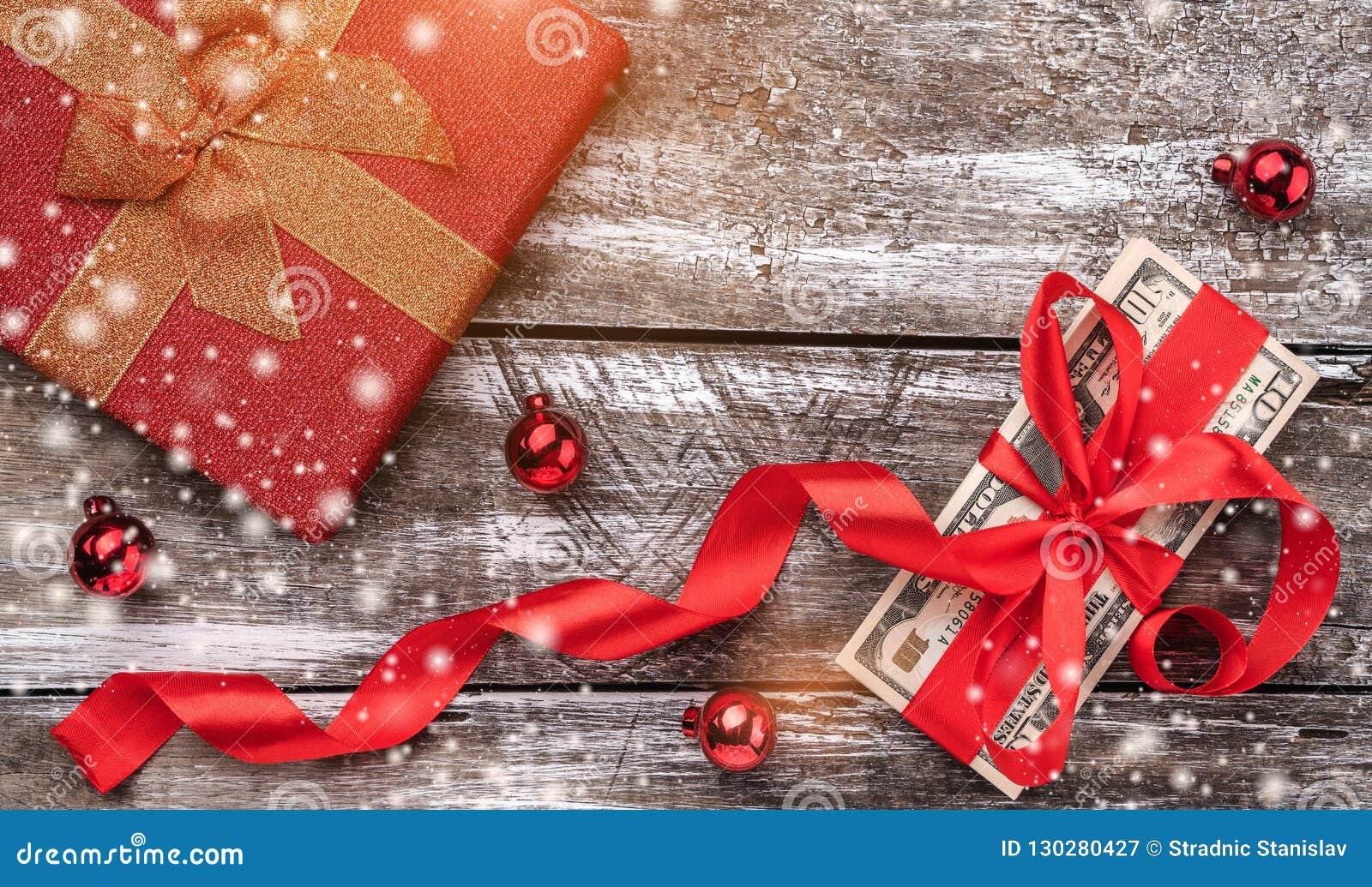 Jul gåva, pengar, Xmas-objekt, på en träbakgrund Top beskådar Effekt av ljus och snöflingor