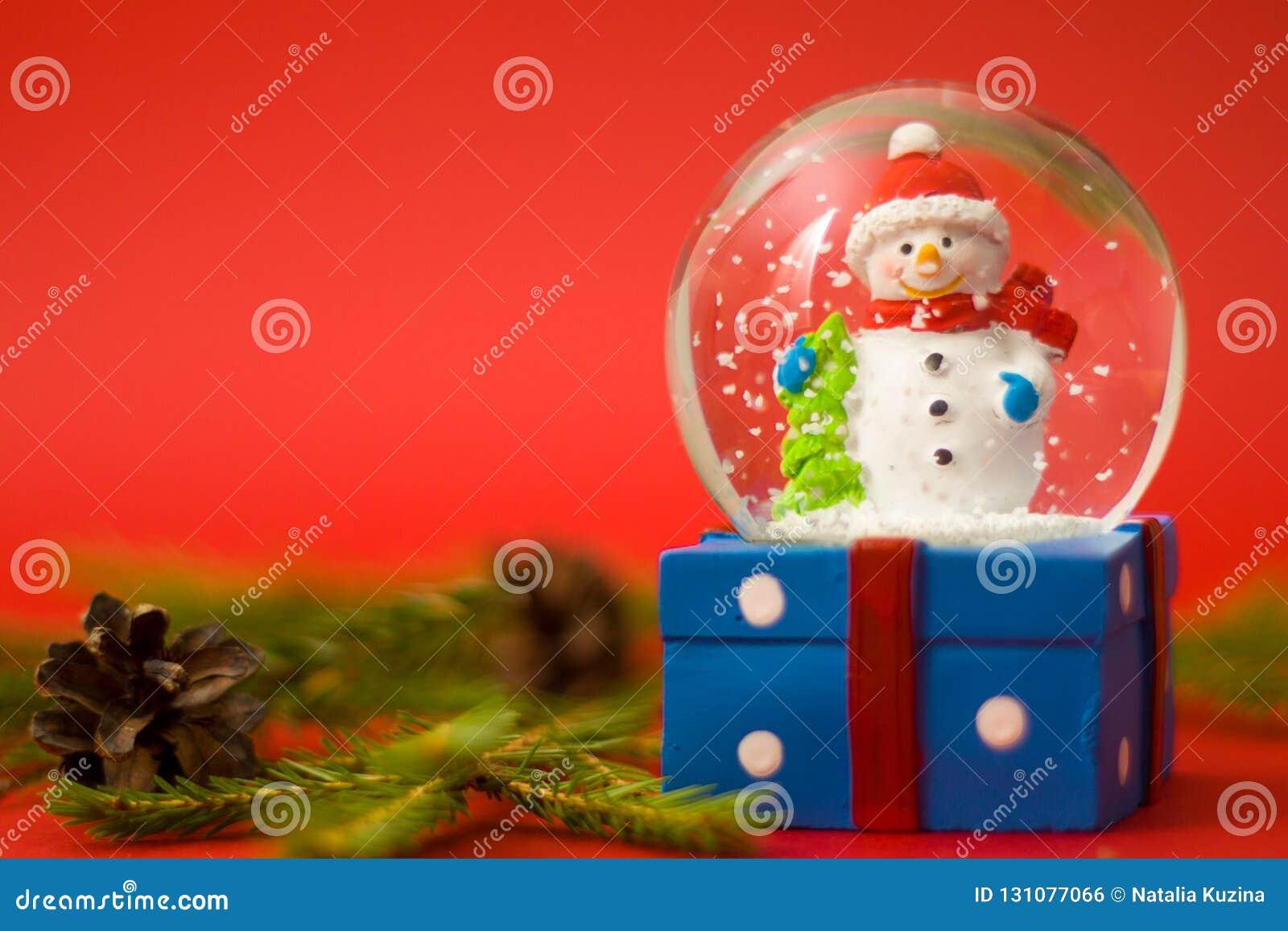 Jul och kort för nytt år med snöjordklotsnögubben inom red för bakgrundsaskgåva Ferier, vinter och berömbegrepp