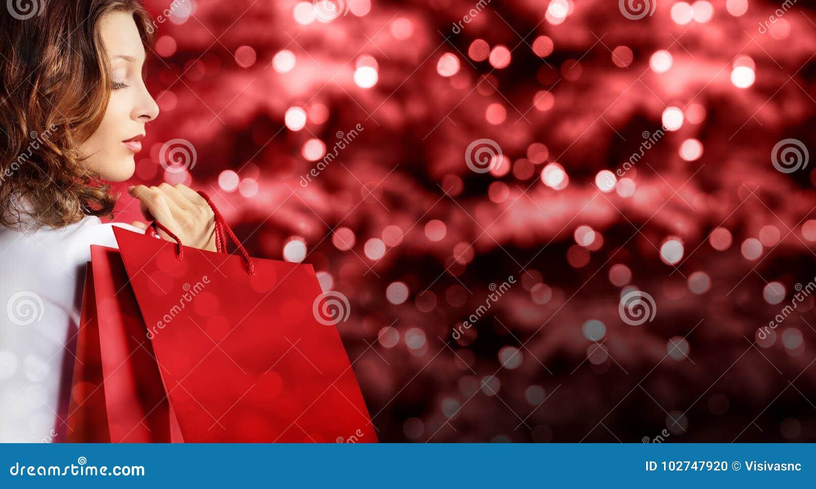 Jul som shoppar, kvinna med påsen på röda suddiga ljusa ljus