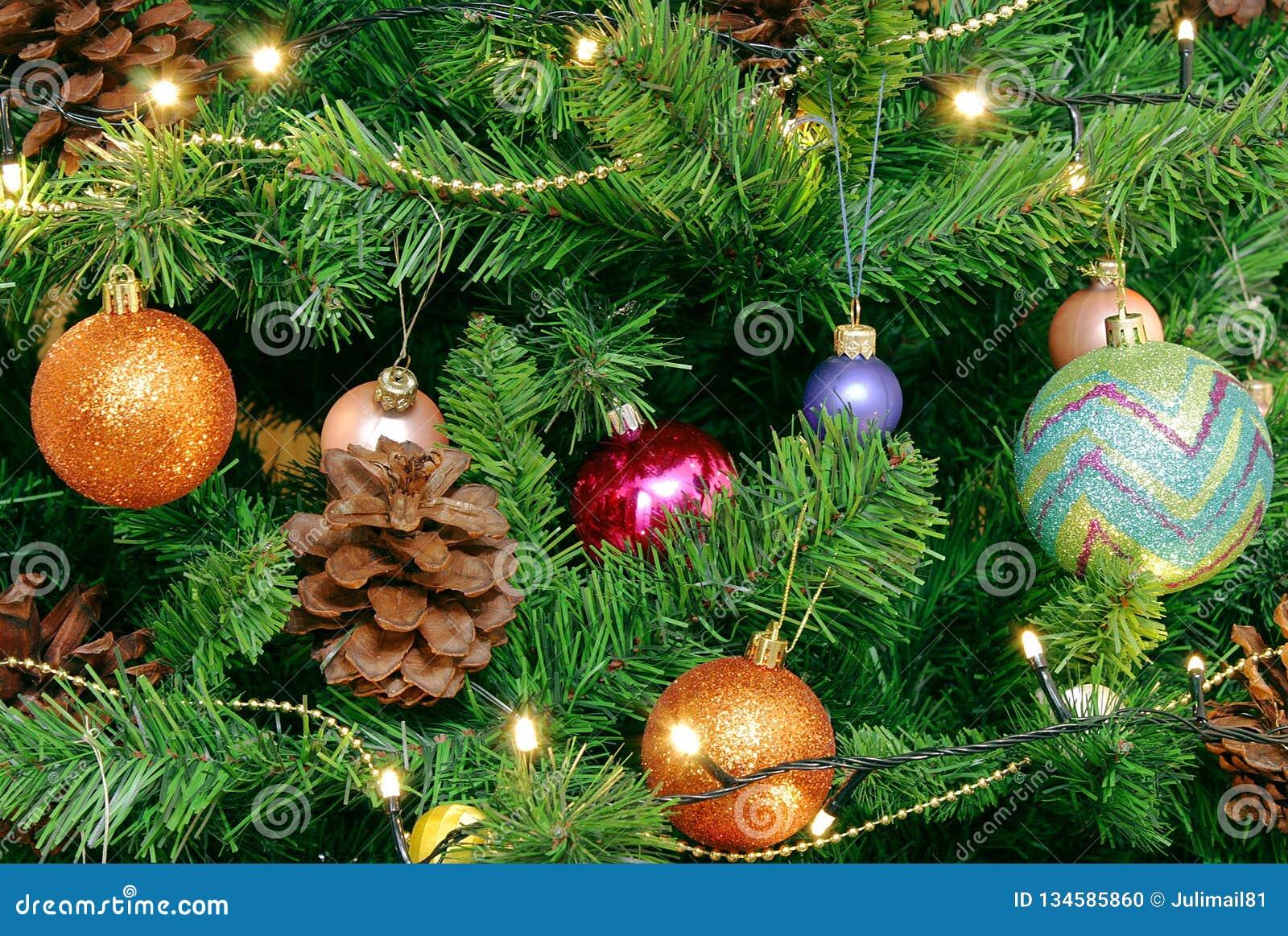Julbakgrund för hälsningkort och platser Grön julgran med stora kottar Dekorerat med ljusa runda bollar, girlander