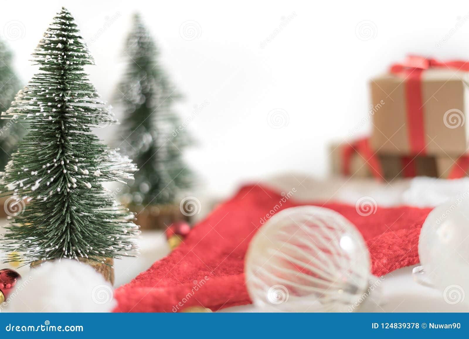 Julbakgrund med jul klumpa ihop sig, gåvaaskar, trädet och den santa hatten på vit bakgrund