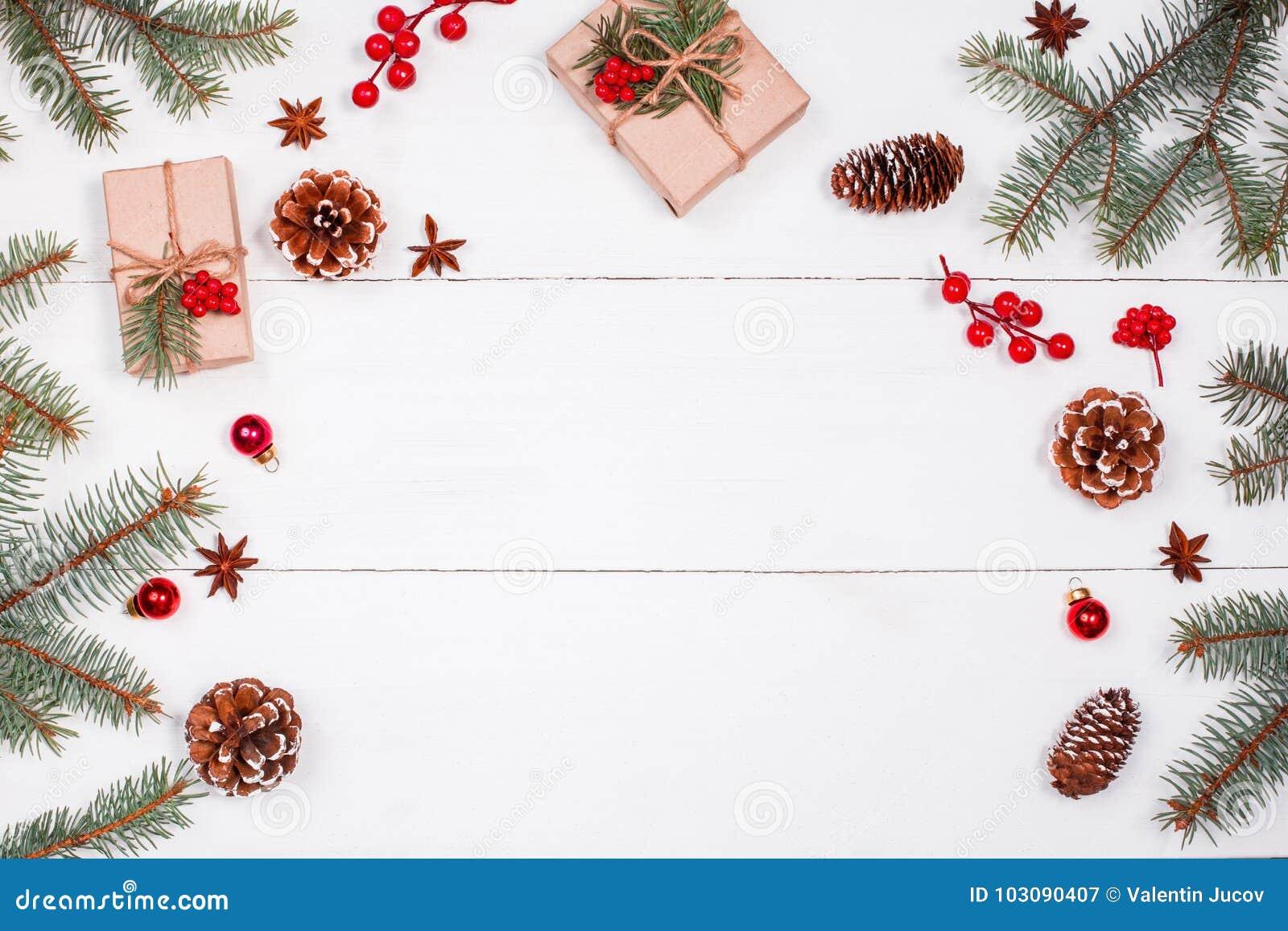 Julbakgrund med julgåvan, granfilialer, sörjer kottar, snöflingor, röda garneringar Xmas och lyckligt nytt år
