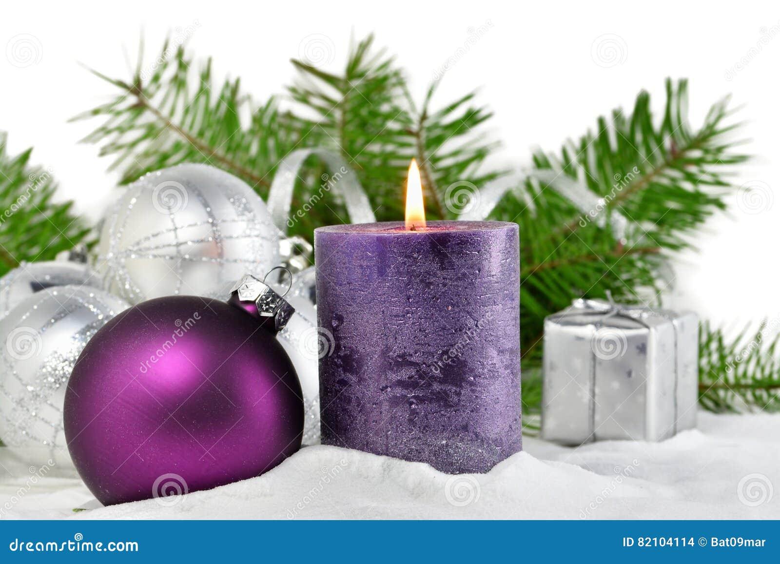 Julbakgrund med stearinljuset och garneringar Lilor och silverjulbollar över granträdfilialer i snön