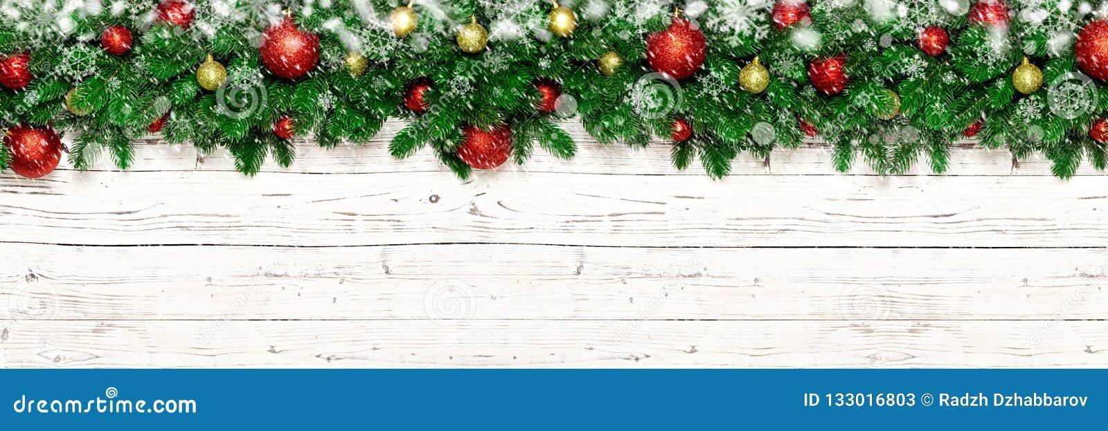Julbaner på vit träbakgrund med snö, snöflinga, granträdfilialer Bästa sikt för Xmas-garnering med kopieringsutrymme