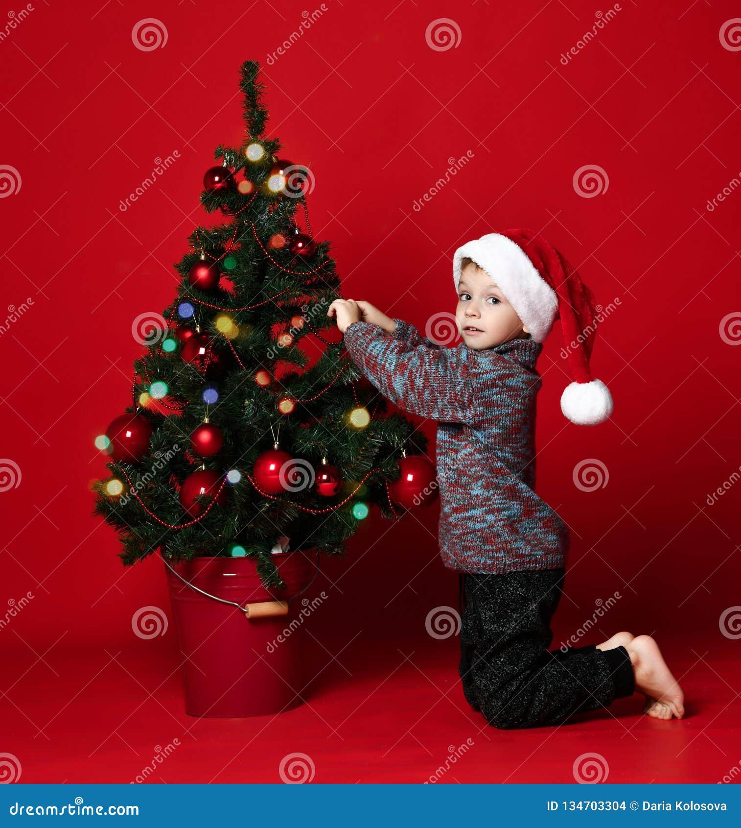 Julfilial och klockor nytt år barnet klär upp en julgran Unge- och julleksaker