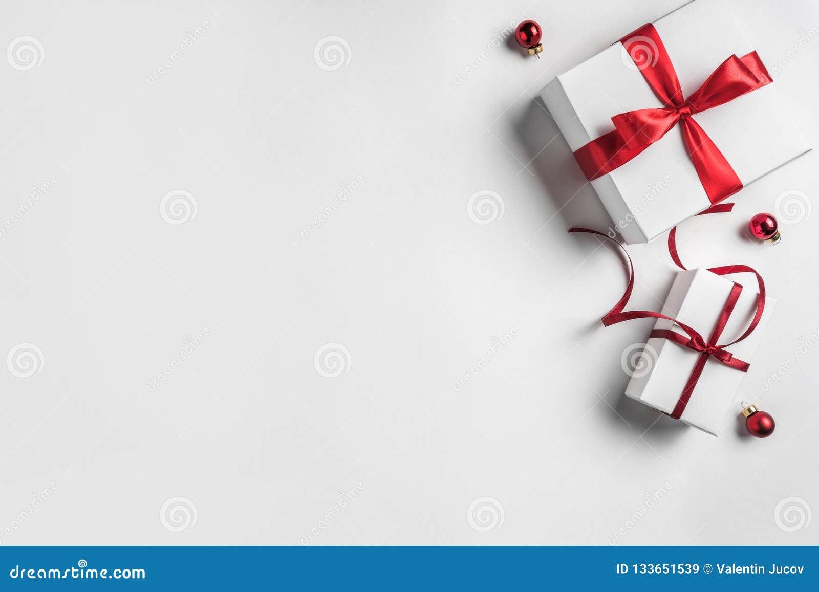 Julgåvaaskar med det röda bandet och garnering på vit bakgrund Tema för Xmas och för lyckligt nytt år