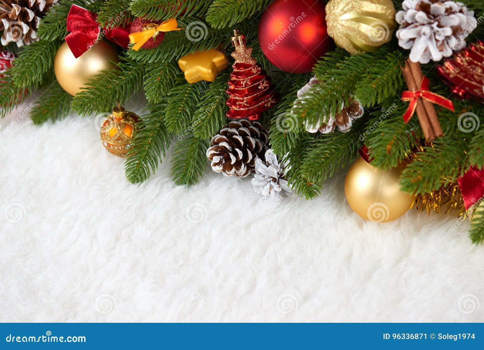 Julgarnering på closeupen för granträdfilialen, gåvor, xmas-bollen, kotten och annat objekt på vitt tomt utrymme pälsfodrar, seme