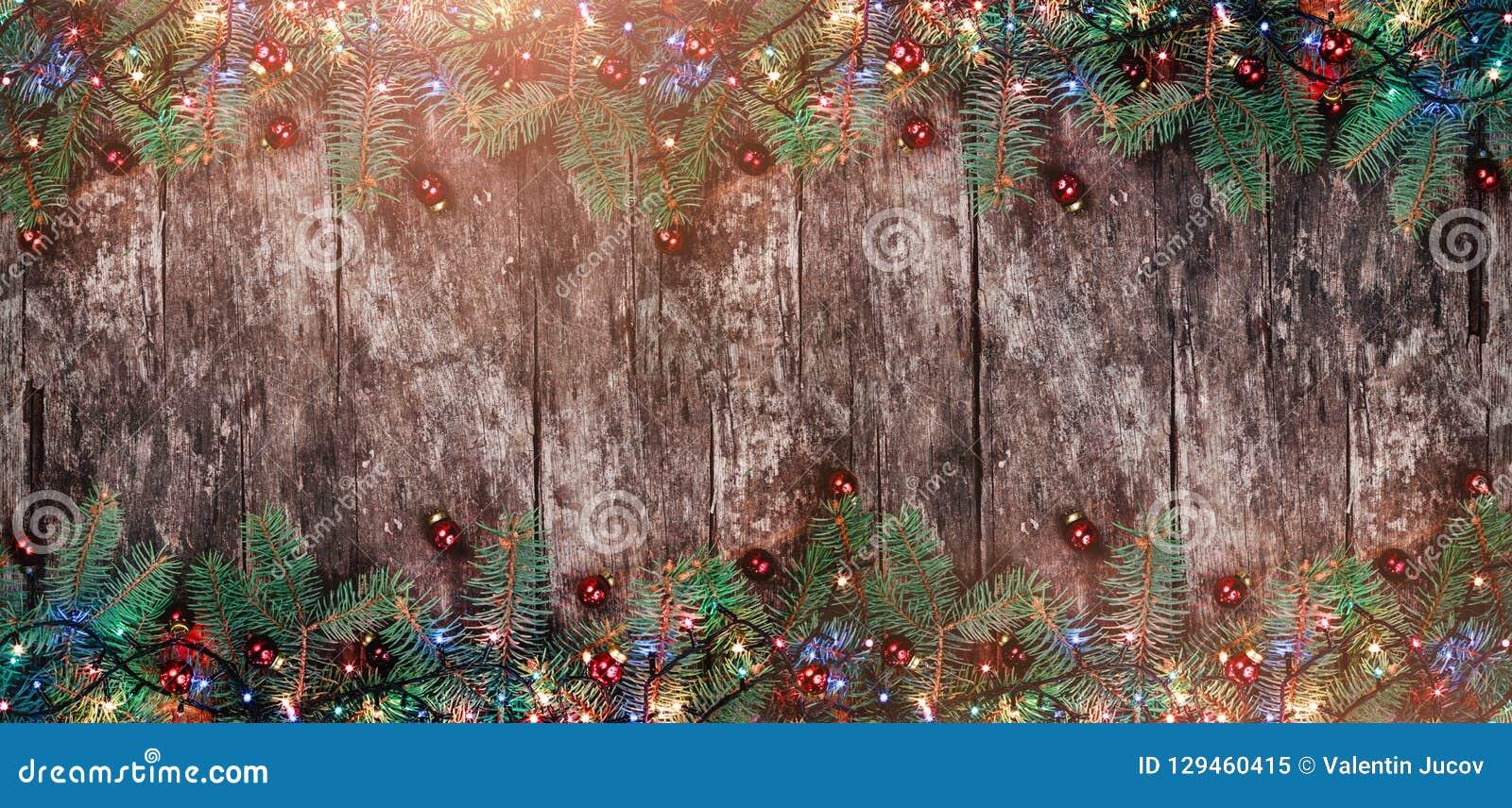 Julgran förgrena sig med ljus och röda garneringar på träbakgrund Ram för Xmas och för lyckligt nytt år