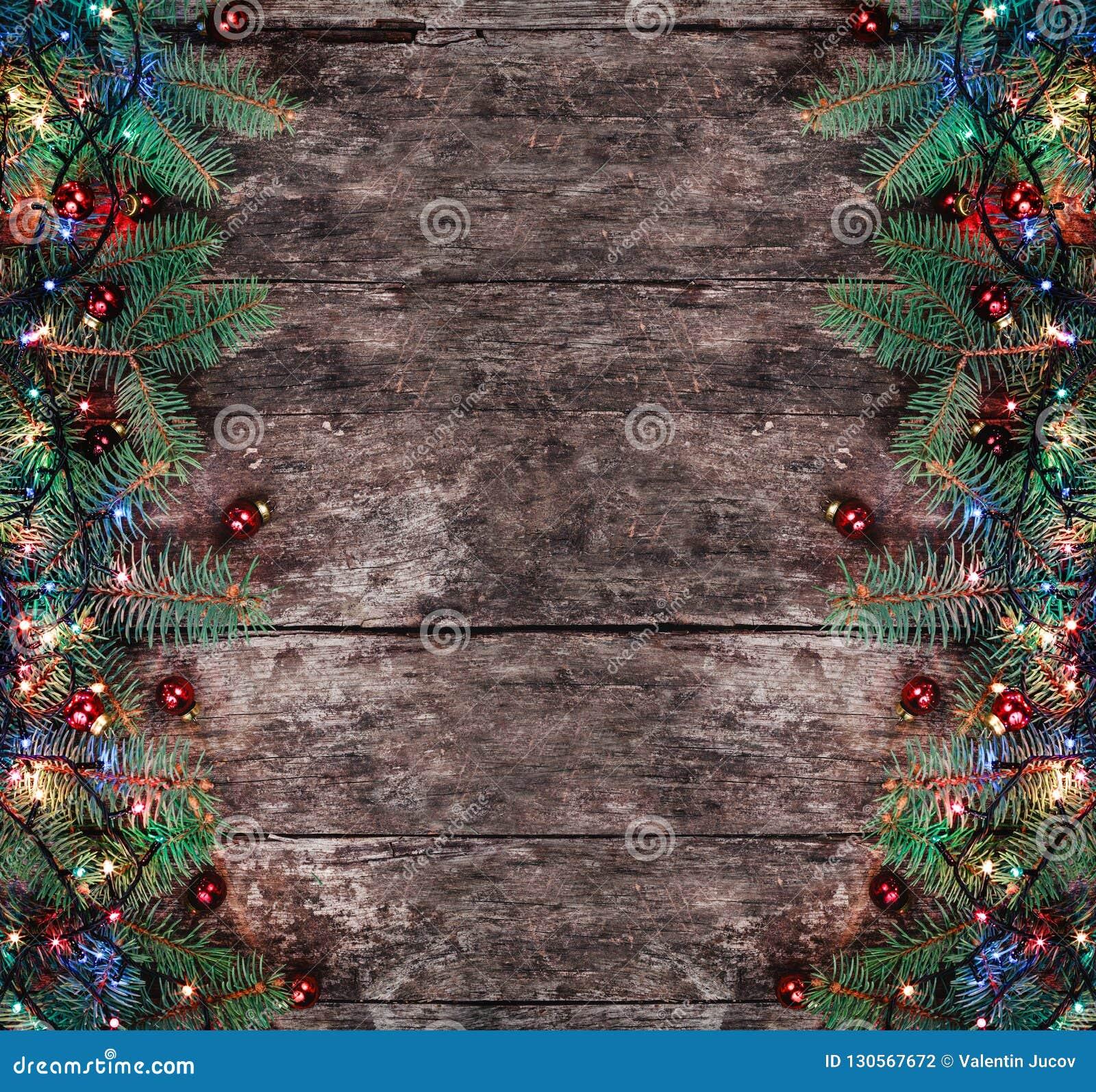 Julgran förgrena sig med ljus och röda garneringar på träbakgrund Sammansättning för Xmas och för lyckligt nytt år