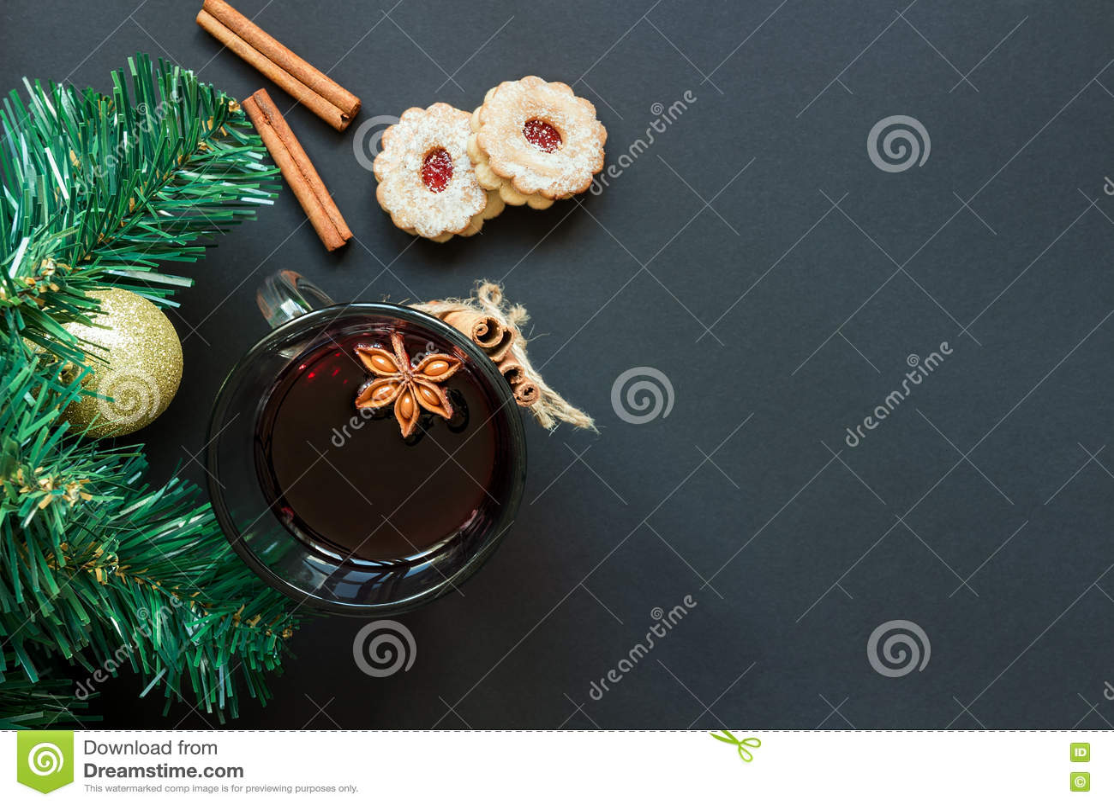 Julgran och vinglas av funderat vin med kakor och apelsinen på den svarta bästa sikten för tabell