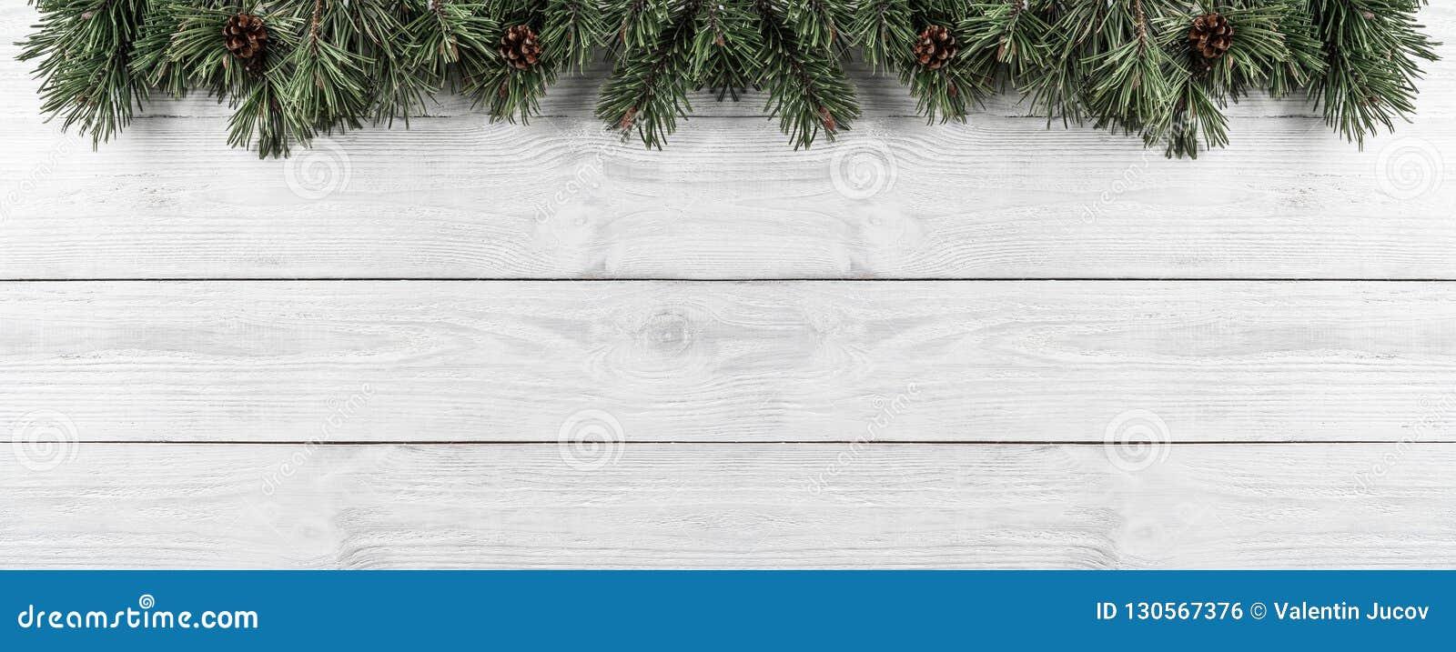 Julgranfilialer med sörjer kottar på vit träbakgrund Tema för Xmas och för lyckligt nytt år Lekmanna- lägenhet, bästa sikt