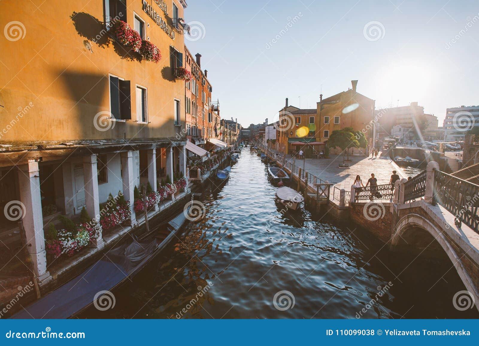22 juli, de schilderachtige zonsondergang van Venetië Italië van 2013 over kanaal met boten onder de oude kleurrijke straten van