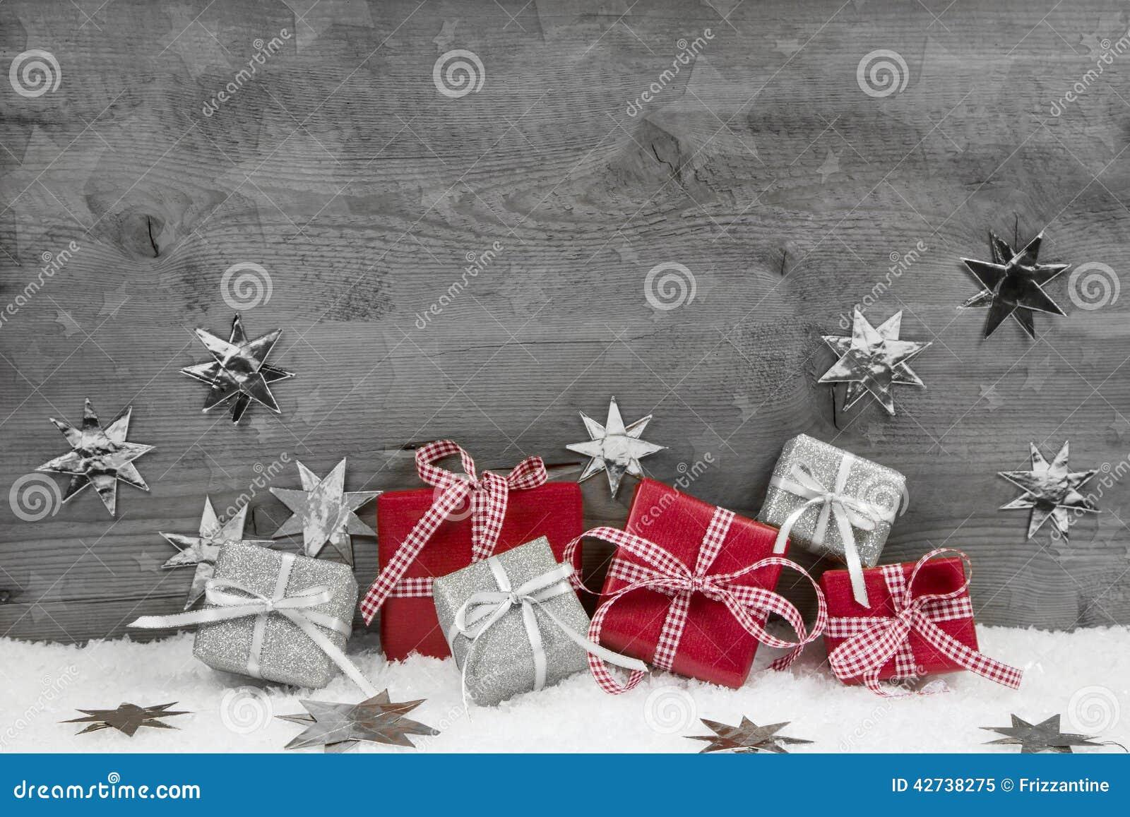 Julklappar i rött och silver på trägrå bakgrund