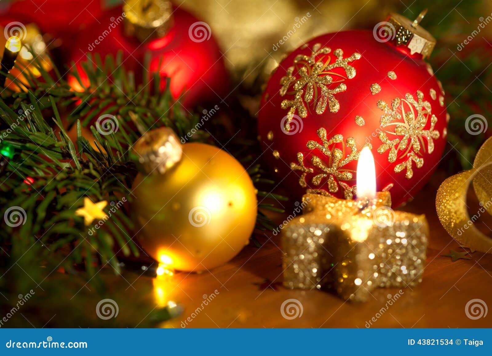 Julkortet med den guld- stearinljuset, bollar, sörjer trädet, ljus och