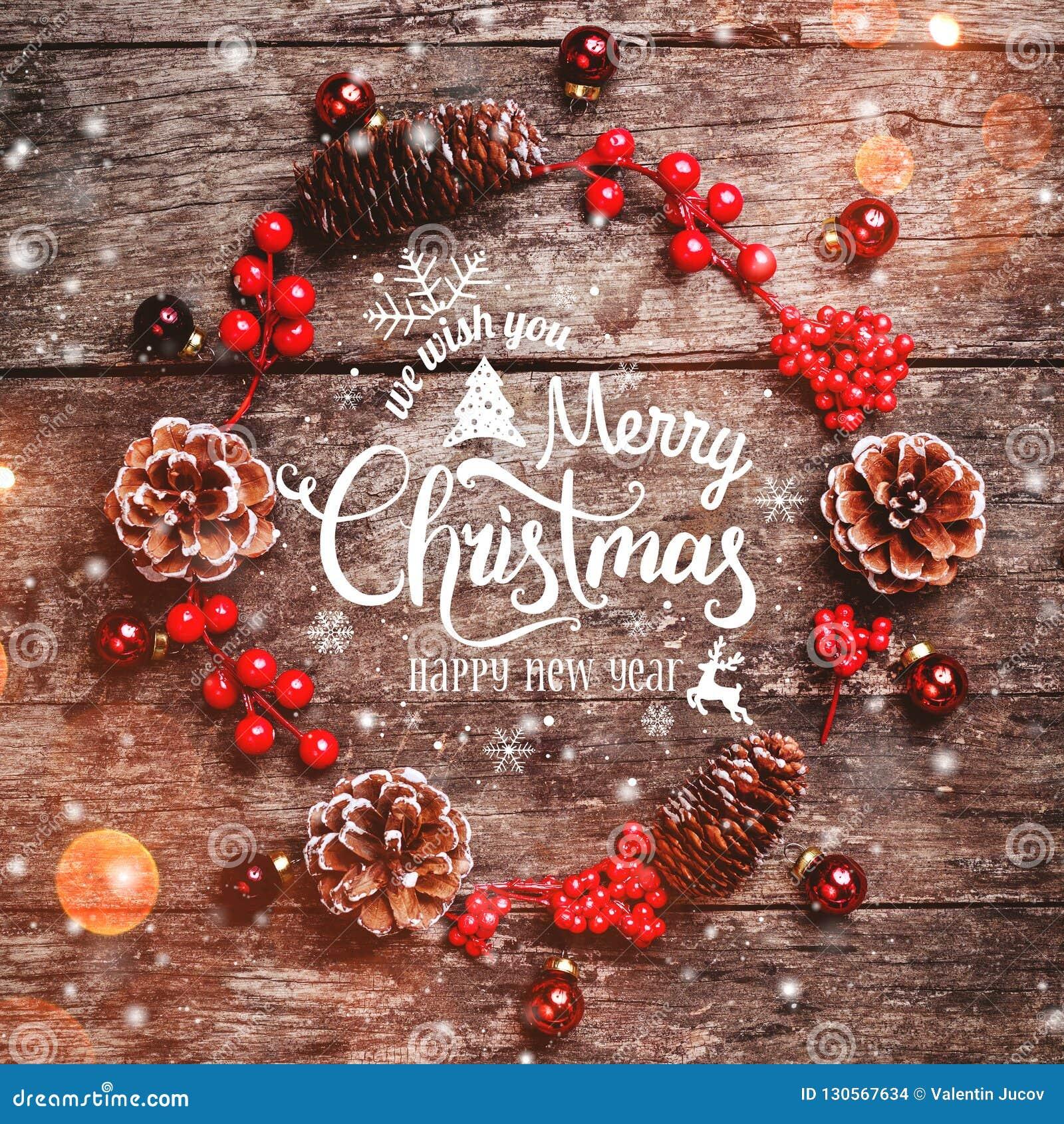 Julkransen av gran förgrena sig, kottar, röda garneringar på mörk träbakgrund Sammansättning för Xmas och för lyckligt nytt år