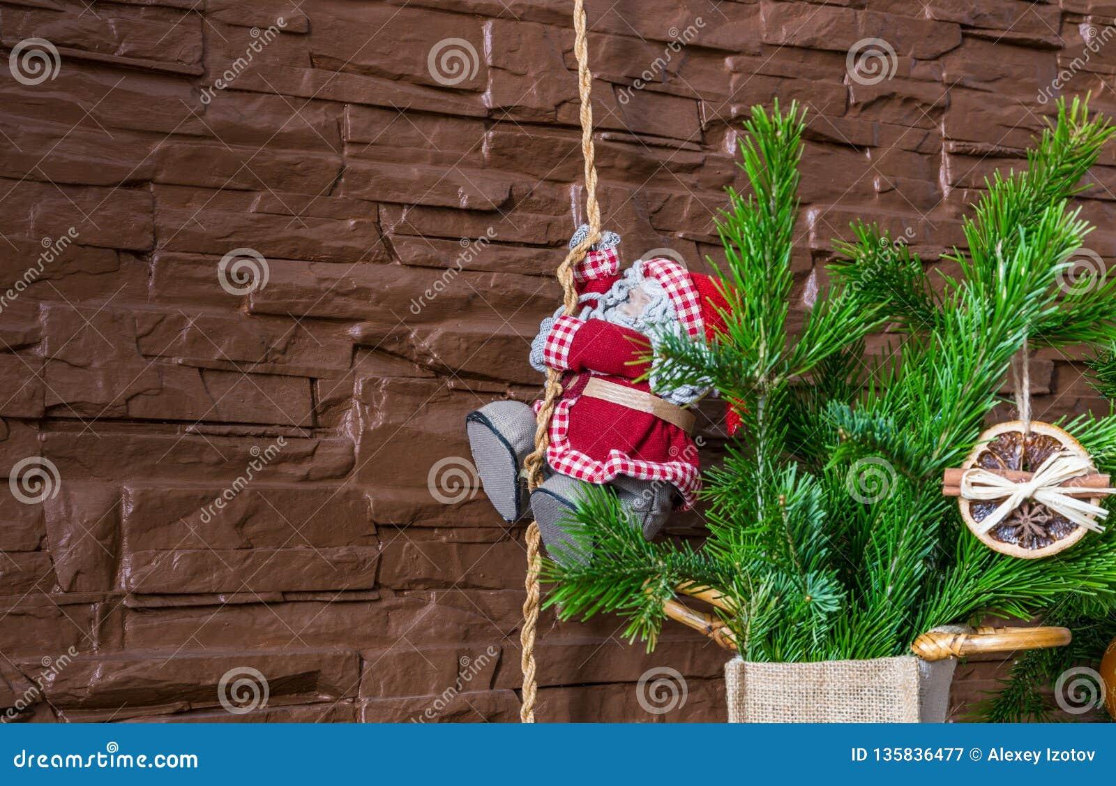 Julordningen av torra orange skivor och kanelbruna pinnar och Santa Claus klättrar repet