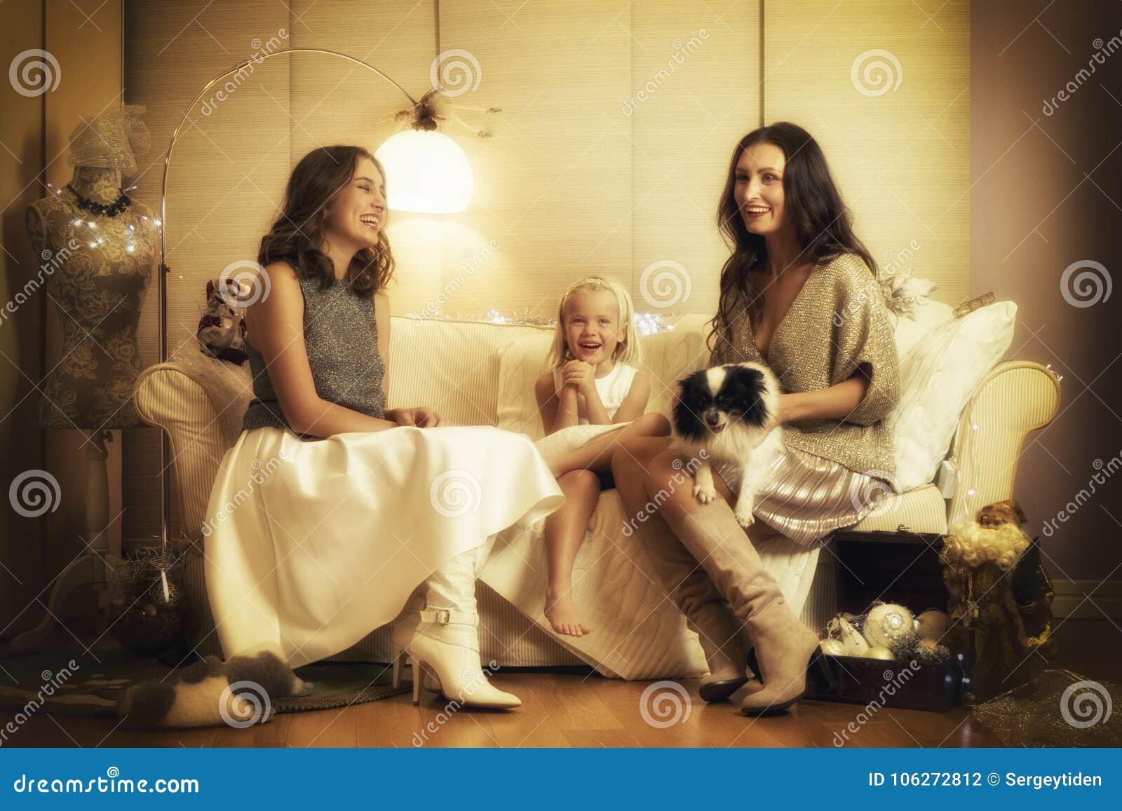 Julphotosession med två flickor, ett barn och en hund i varm ljus studio
