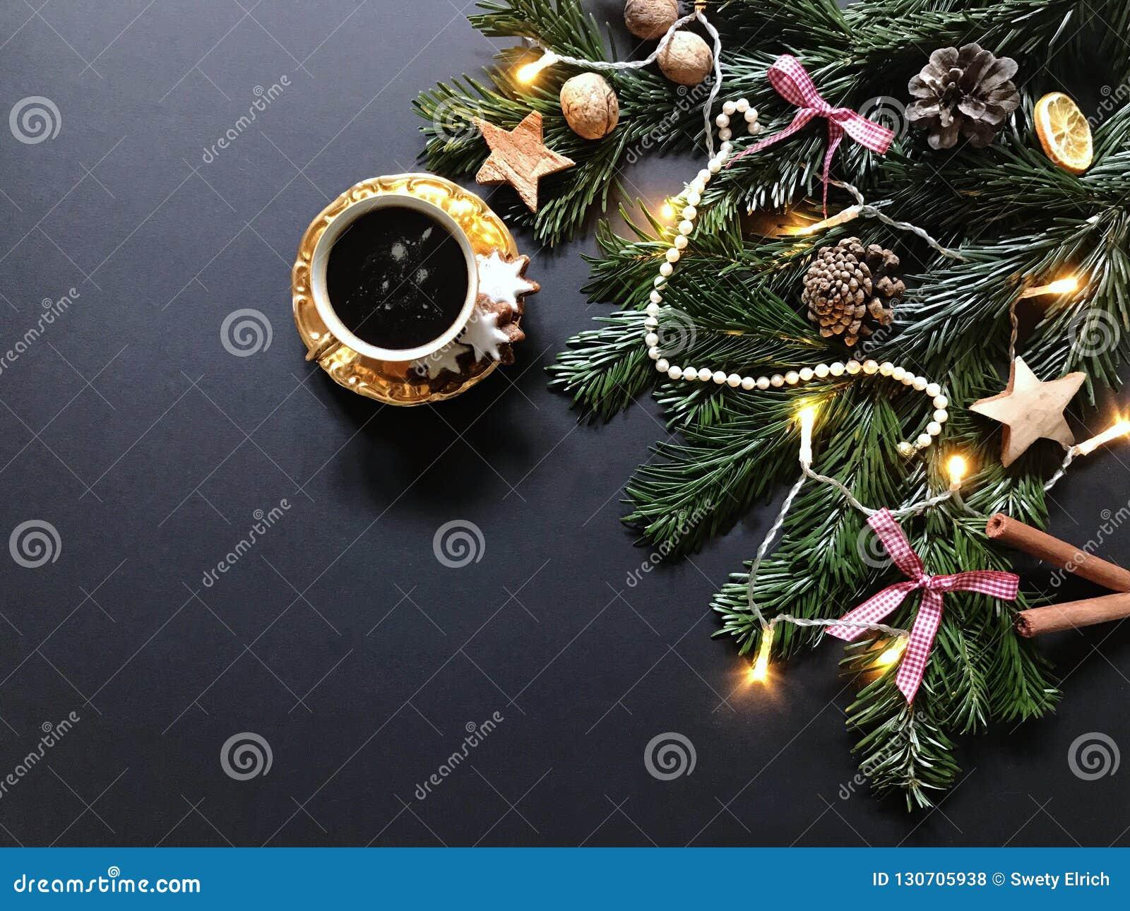 Julsammansättning med granträdfilialer och julpynt, en kopp kaffe med kanelbruna kakor
