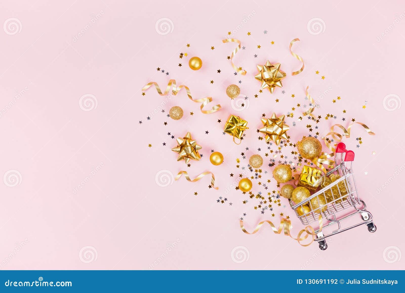 Julshoppingvagn med gåvan, feriegarneringar och guld- konfettier på bästa sikt för rosa pastellfärgad bakgrund lekmanna- stil för