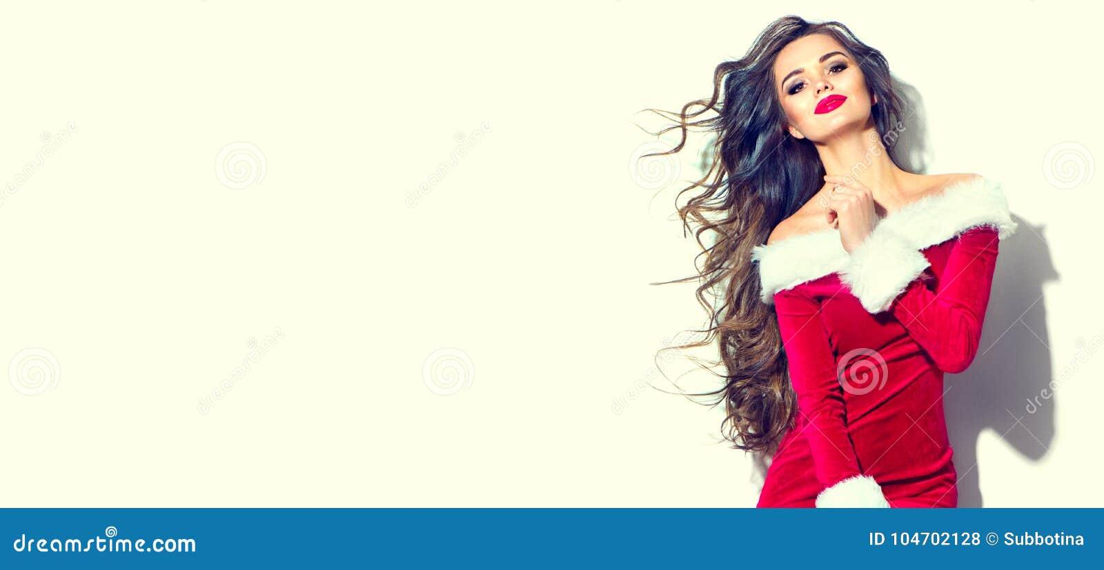 Julskönhetflicka Ung kvinna för sexig brunett som bär den röda santa klänningen