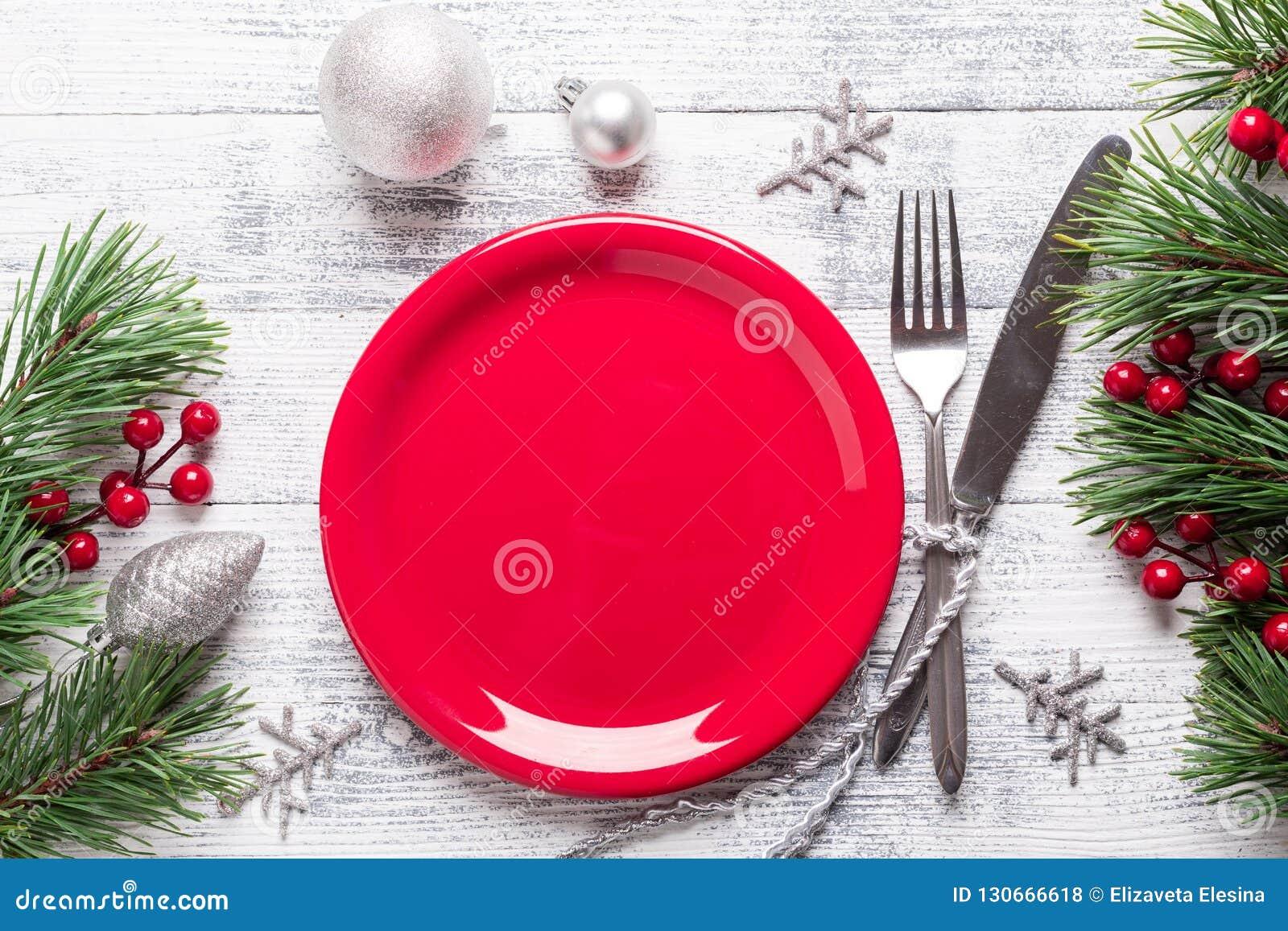 Jultabellinställning med den tomt rött plattan, gåvaasken och bestick på ljus träbakgrund tät grantree för filial upp