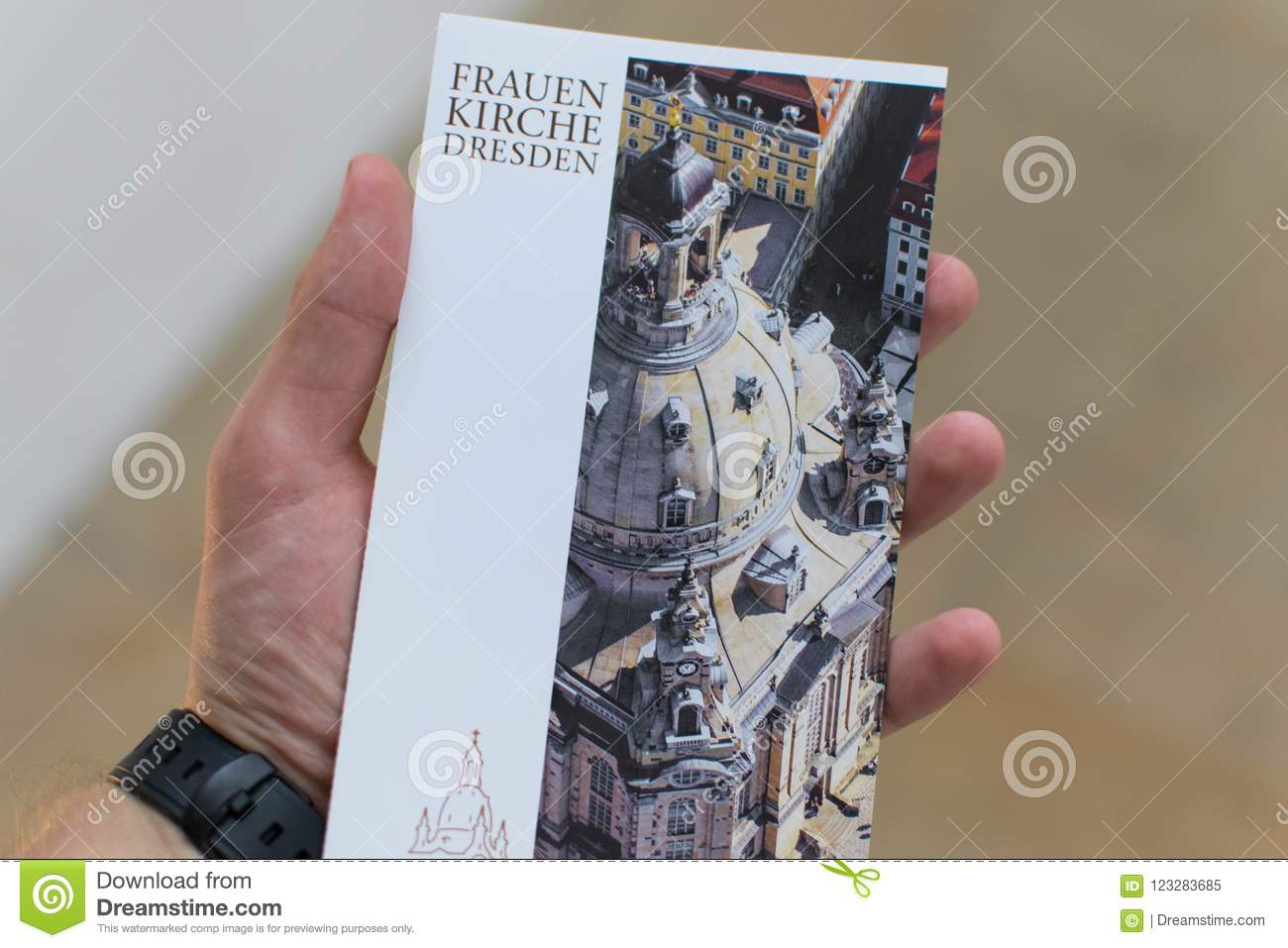July 20, 2007 Dresden. Germany Church of the Frauenkirche. A postcard with the history of the church in the hands.