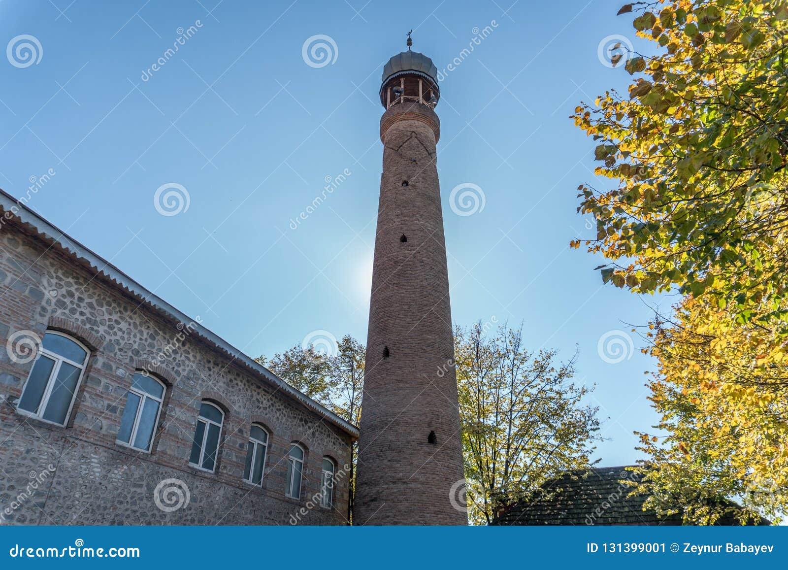 Juma Mosque minaret against solid blue skey.