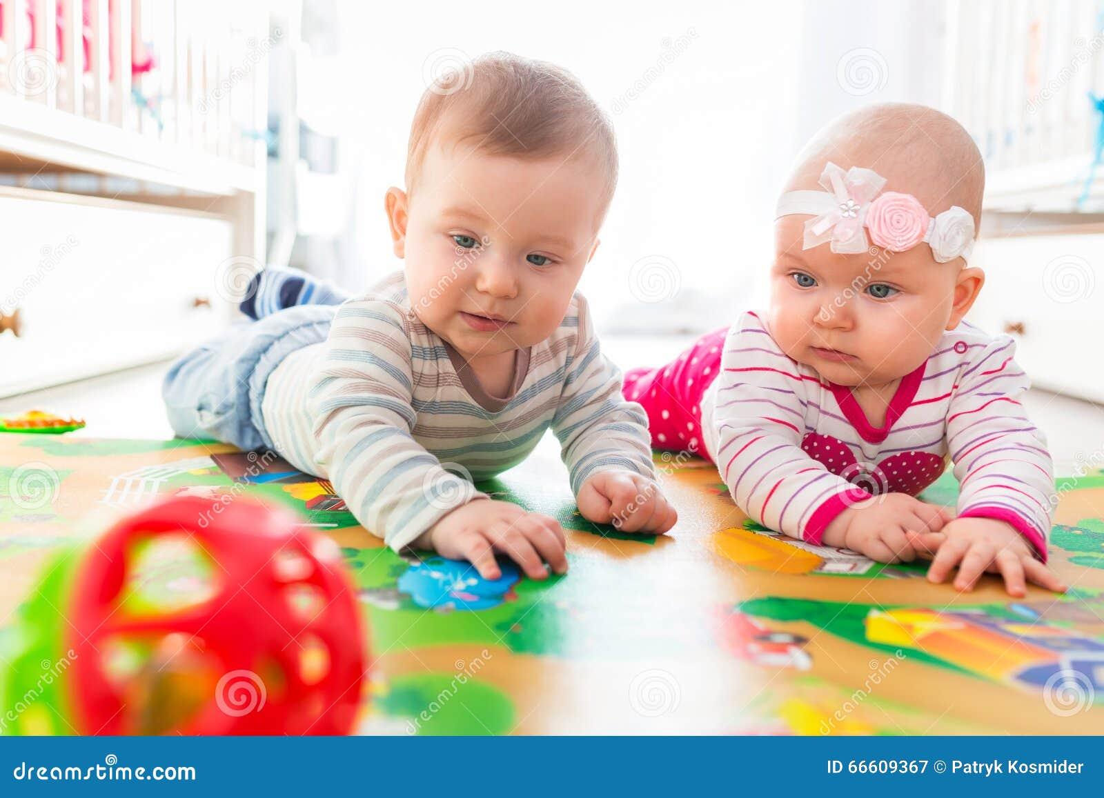 Les Bébés Filles Jumeaux : Jumeaux de bébé garçon et fille jouant avec la boule