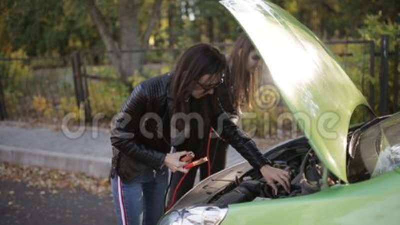 Two Not Too Bright Girls Trying To Recharge A Dead Car Battery Two Girls At The Open Hood Of A Car Trying To Connect To Breakdown Discharged