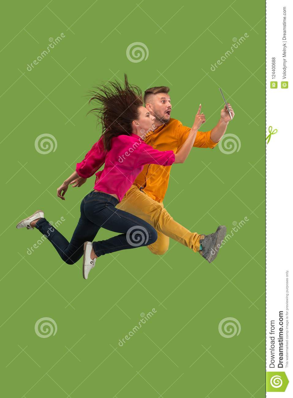 Jump of young couple over green studio background using laptop or tablet gadget while jumping.