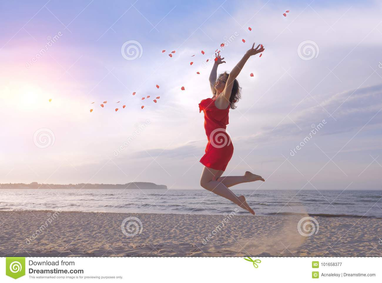 Jumping beautiful woman in red dress throwing rose petals on beach.