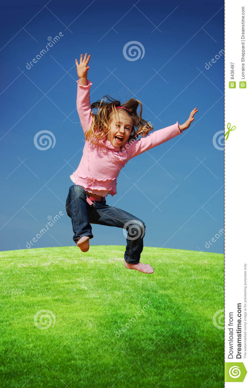 view of a little girl jumping with joy on a grassy landscape.