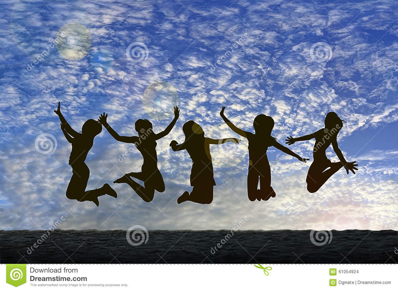 Girls jumping with Joy on the beach silhouetted against a cloudy sky