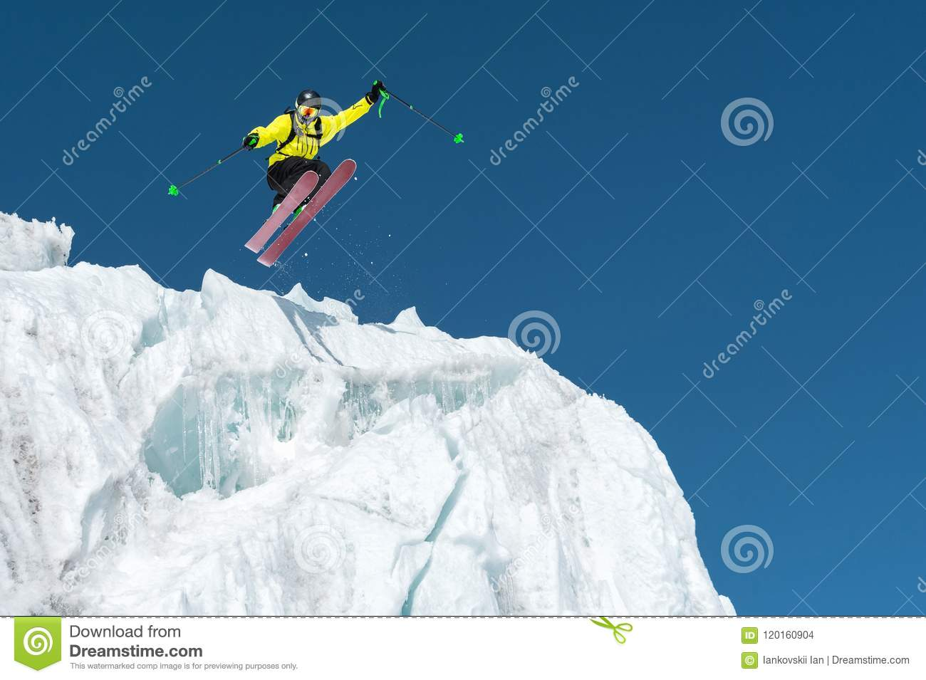 A jumping skier jumping from a glacier against a blue sky high in the mountains. Professional skiing