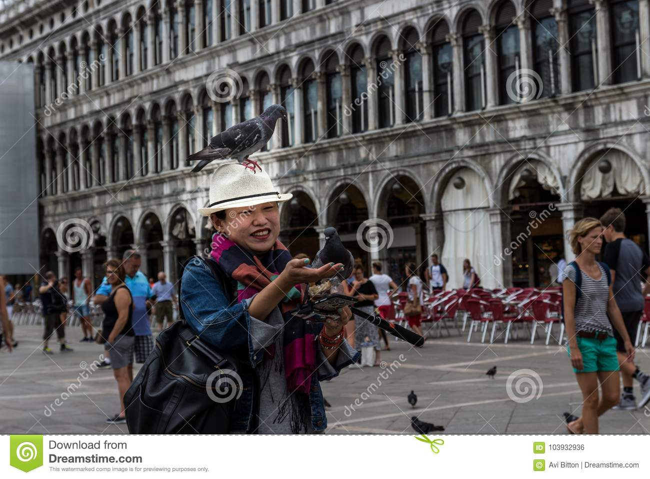 27 of June, St. Marks Square, Venice, Italy: Some pigeons are sitting on a Japanese women`s hat, that tried to feed them at he sq