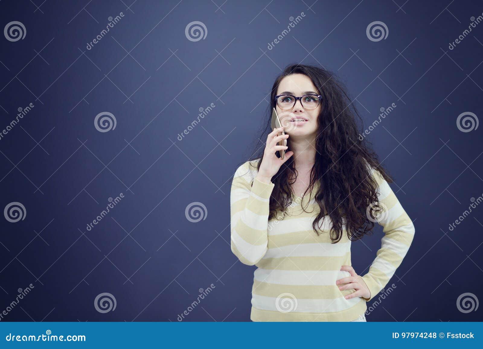 Junge, überzeugte, erfolgreiche und schöne Geschäftsfrau mit dem Handy lokalisiert