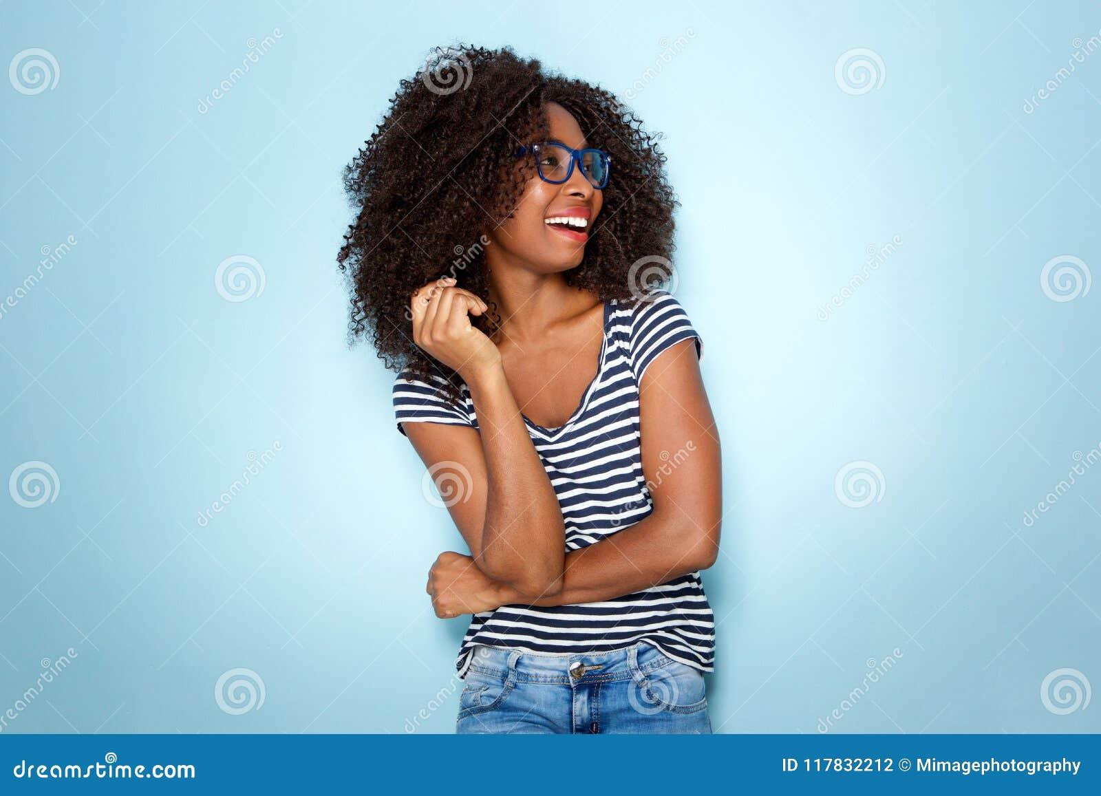 Junge Afroamerikanerfrau, die mit Gläsern auf blauem Hintergrund lächelt