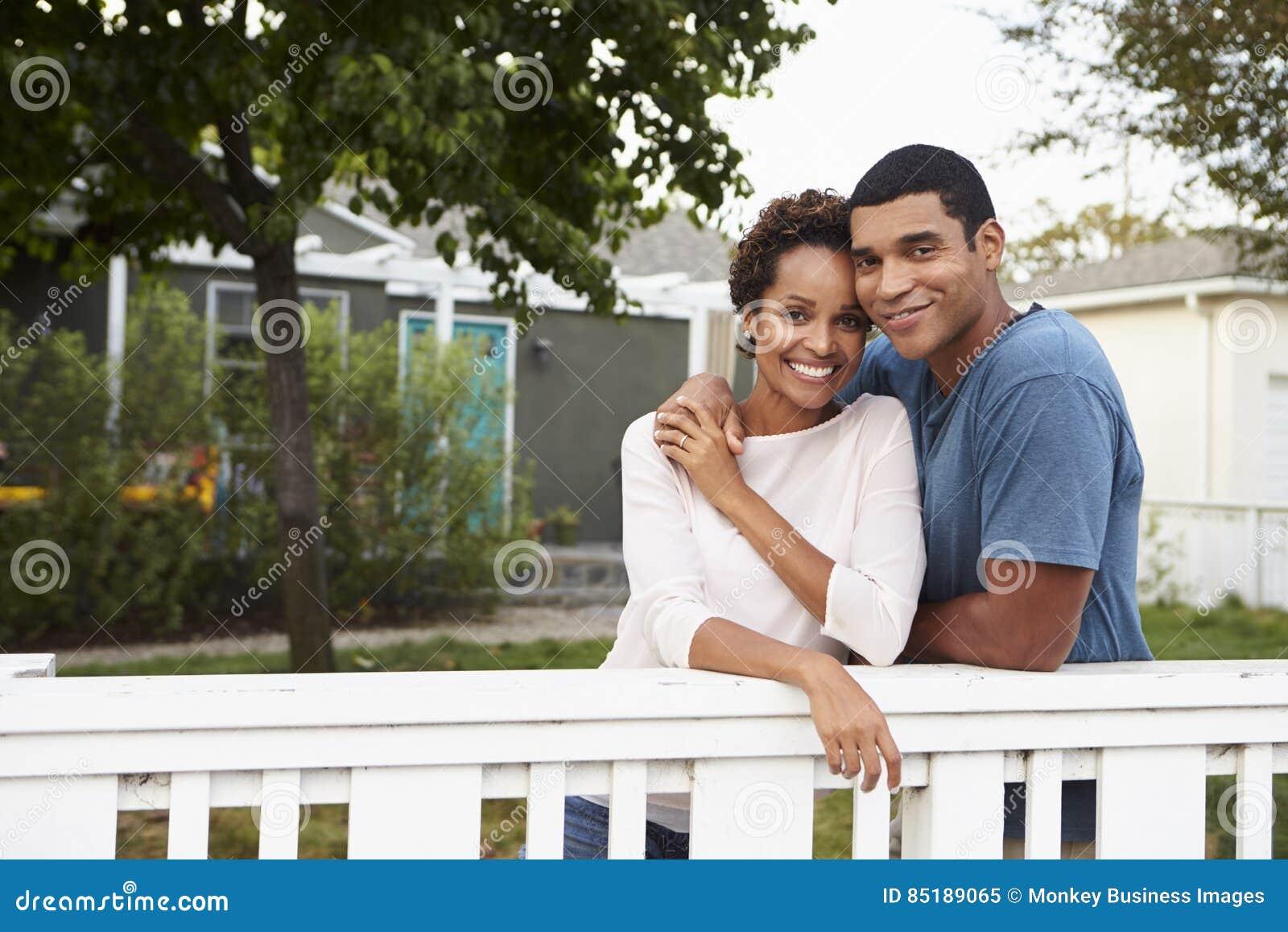 Junge Afroamerikanerpaarumarmung außerhalb ihres Hauses