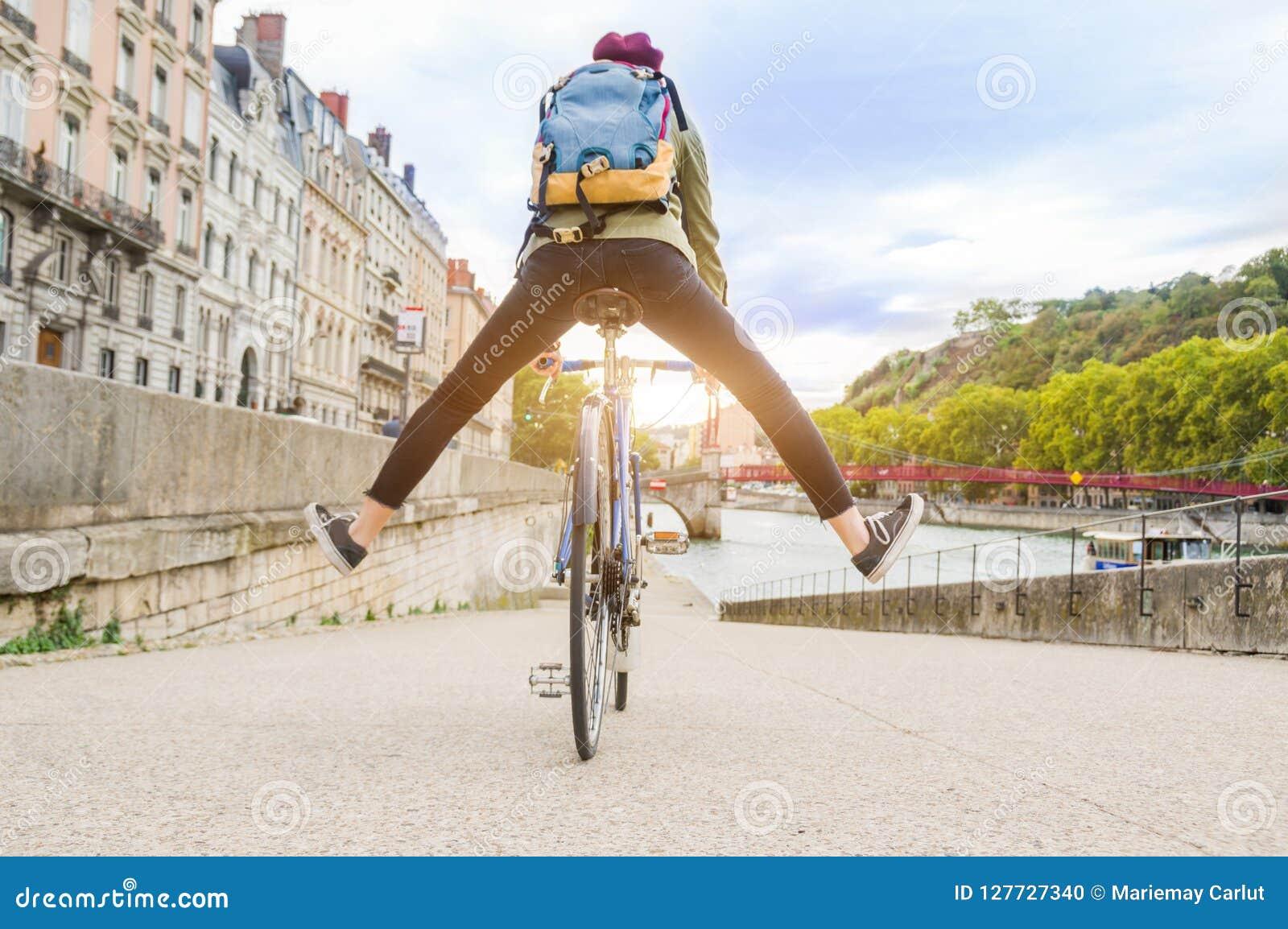 Junge aktive Frau, die Fahrrad hinuntergeht die Straße in der Stadt fährt