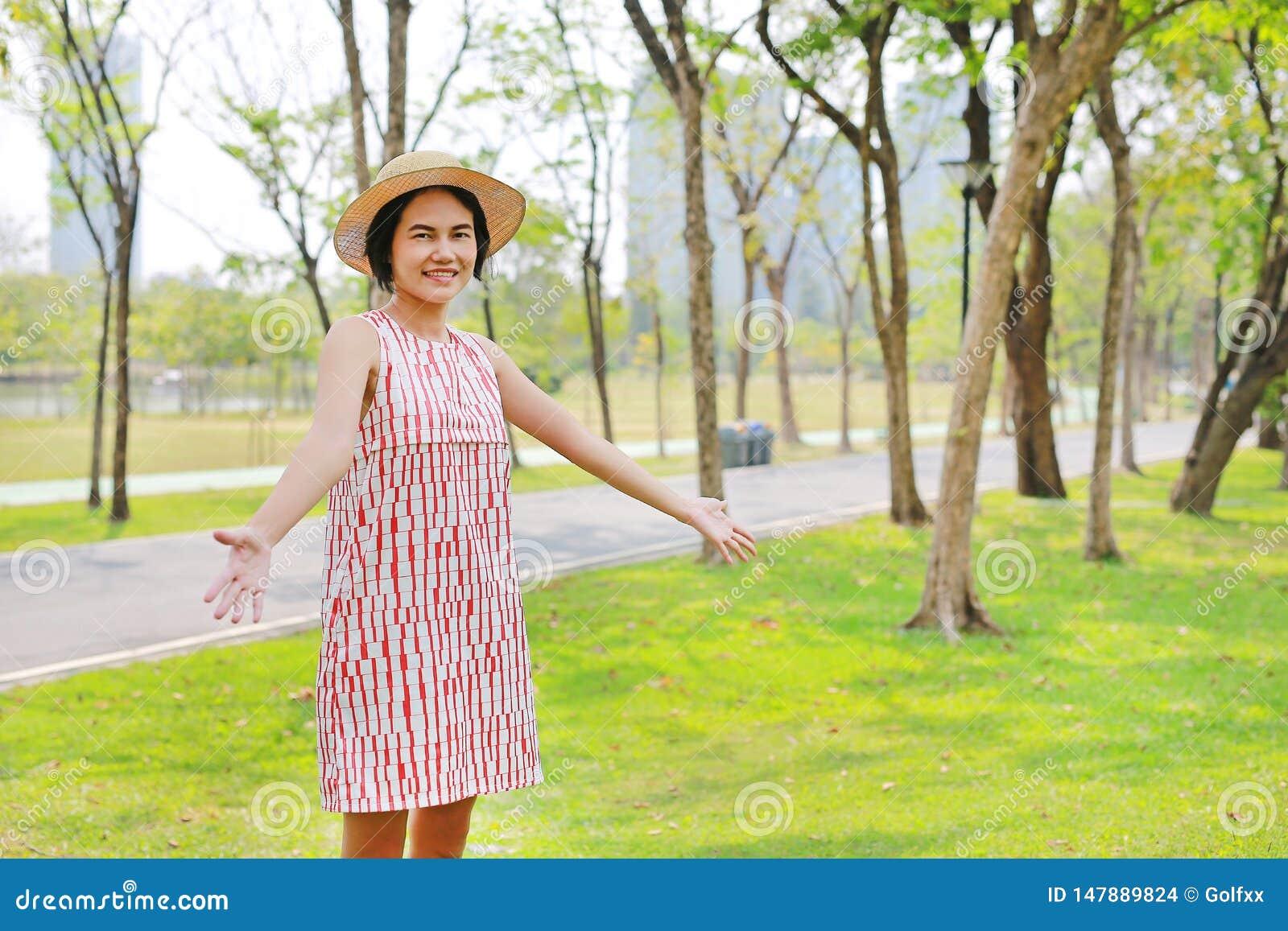 Junge Asiatin, die Arme und Lächeln im Naturpark anhebt