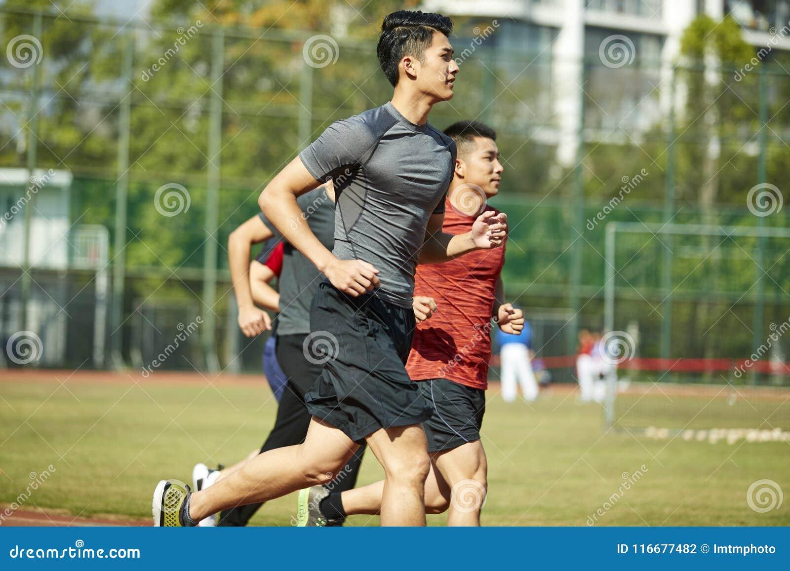 Junge asiatische Athleten, die auf Bahn laufen