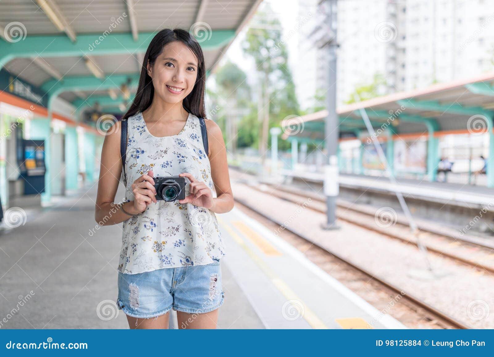 Junge asiatische Frau, die Digitalkamera im hellen Bahnhof hält