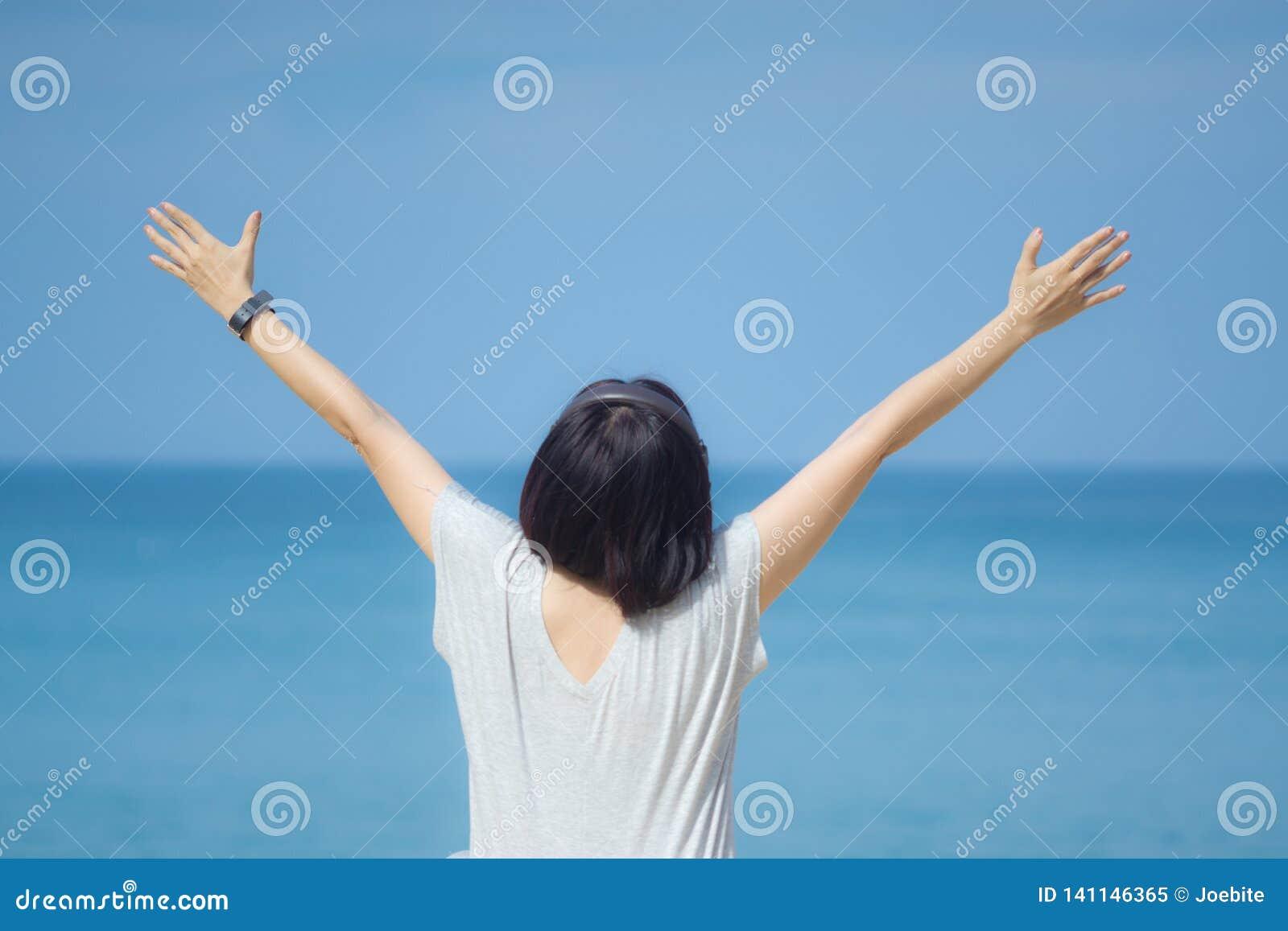Junge asiatische Frau im grauen Kleiderhändchenhalten bis zum Himmel Blauer Himmel und Kristallmeer des tropischen Strandes als H