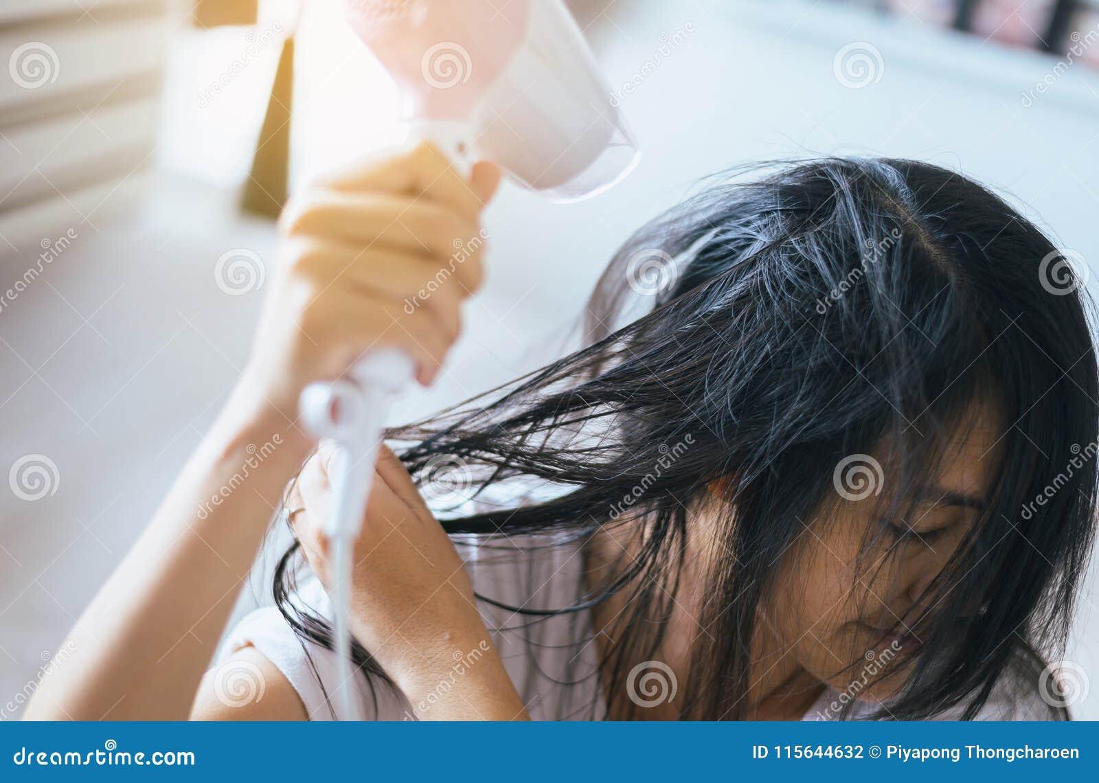 Junge asiatische Frau nach dem Bad, das ihr Haar mit Kamm, weiblicher Trockner ihr langes Haar mit Trockner hairbrushing ist