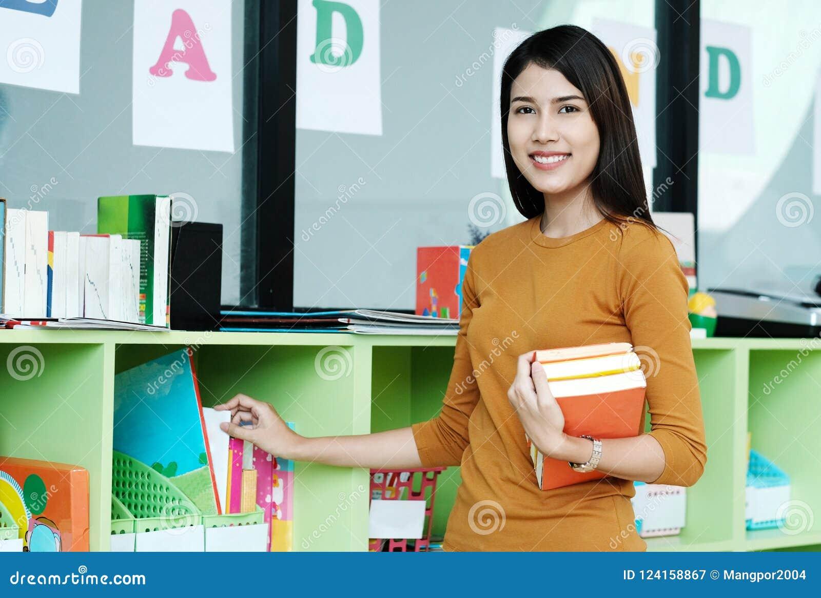 Junge asiatische Frau, welche die Bücher stehen am Bibliothekshintergrund hält,
