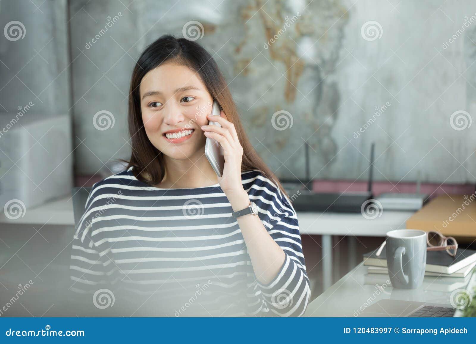 Junge asiatische Geschäftsfrau, die Smartphone verwendet, um auf cust einzuwirken